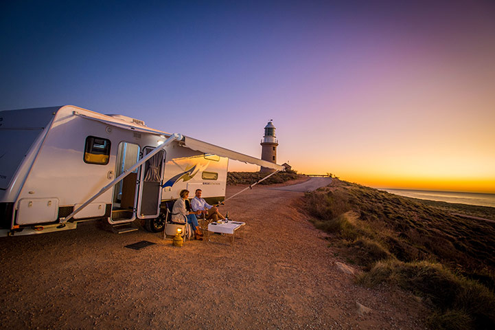 Couple with Caravan from Get Hitched Caravan Hire watching the sunset at Vlamingh Head Lighthouse